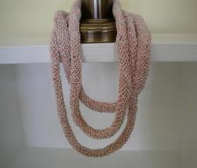3 strand hand knit necklace of salmon pink and ivory colored yarns.